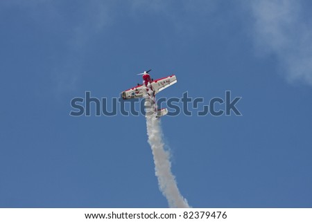 BANESTI, ROMANIA - AUGUST 6: Sukhoi Su-26 piloted by Jurgis Kairys from Lithuania during Banesti airshow 2011 on August 6, 2011 in BANESTI, ROMANIA - stock photo