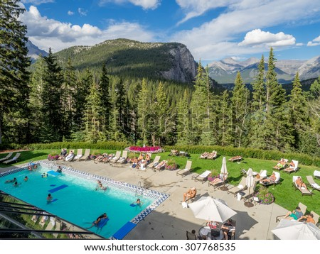 BANFF, CANADA - AUG 9, 2015: Outdoor pool at the Banff Springs Hotel on August 19, 2015 in the Canadian Rockies. The Banff Springs Hotel was built during the 9th century in Scottish Baronial style. - stock photo