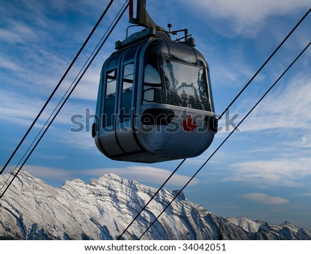 Banff Sulphur Mountain Gondola on a blue sky with snow peaked Rocky Mountains in background. - stock photo