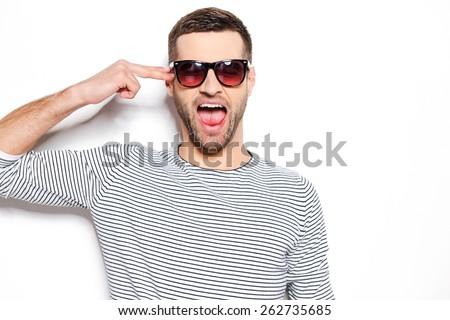 Bang! Excited young man gesturing and keeping mouth open while standing against white background  - stock photo