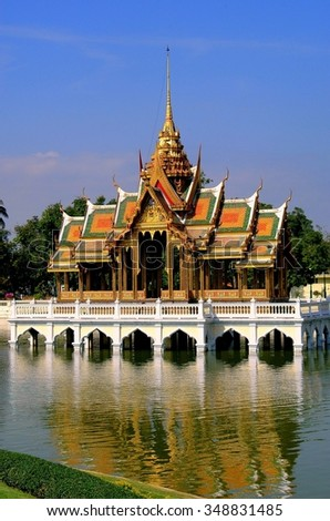 Bang Pa-In, Thailand - December 27, 2005: Phra Thinang Aisawan Tippaya, a jewel of Thai architecture wit chofahs, gabled roofs, and gilded spire, in the middle of a lake at the summer royal palace