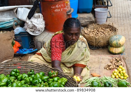 BANGALORE, IN - JUNE 26: Vendor sells produce on an unnamed street in Bangalore, IN June 26, 2011 in Bangalore, India. 42% of India falls below the international poverty line of $1.25 a day. - stock photo