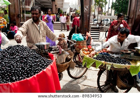BANGALORE, IN - JUNE 26: Vendors selling fruit on an unnamed street in Bangalore, IN June 26, 2011 in Bangalore, India. 42% of India falls below the international poverty line of $1.25 a day. - stock photo