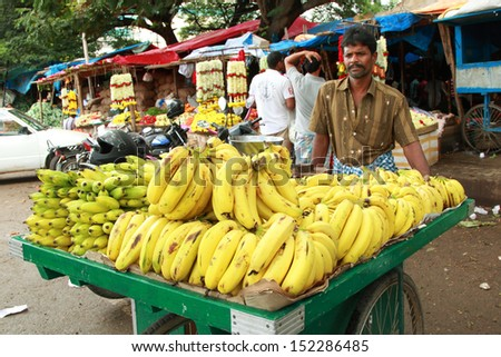 BANGALORE, INDIA - AUGUST 25: Unidentified street seller  selling banana on a city street on August 25, 2013 in Madiwala market, Bangalore, Karnataka, India. - stock photo