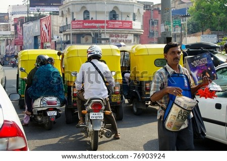 BANGALORE, INDIA - MAR 21: Auto rickshaws, motorbikes, cars fill India's streets March 21, 2011 in Bangalore. These iconic taxis have recently been fitted with CNG powered engines to reduce pollution. - stock photo
