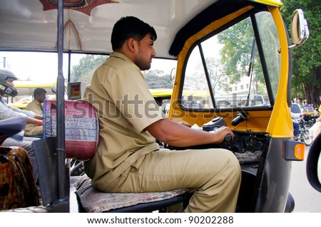 BANGALORE, INDIA - MARCH 21: Auto rickshaw taxi driver on March 21, 2011 in Bangalore, India. These iconic taxis have recently been fitted with CNG powered engines in an effort to reduce pollution. - stock photo