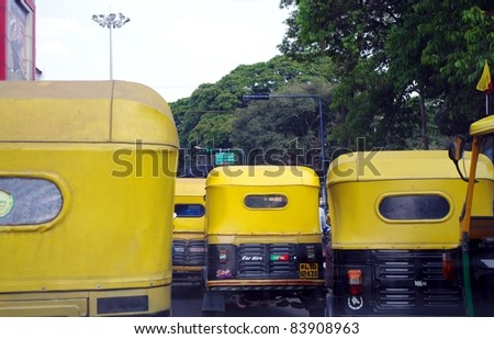 BANGALORE, INDIA - MARCH 21: Auto rickshaw taxis on a road on March 21, 2011 in Bangalore, India. These iconic taxis have recently been fitted with CNG powered engines in an effort to reduce pollution