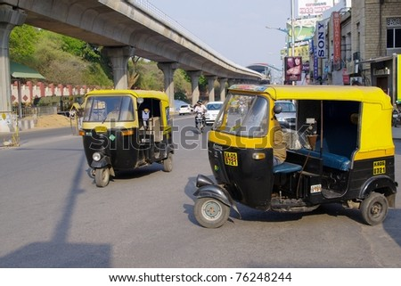 BANGALORE, INDIA - MARCH 21: Auto rickshaw taxis on March 21, 2011, M.G. road, Bangalore, India. These iconic taxis have recently been fitted with CNG powered engines in an effort to reduce pollution.