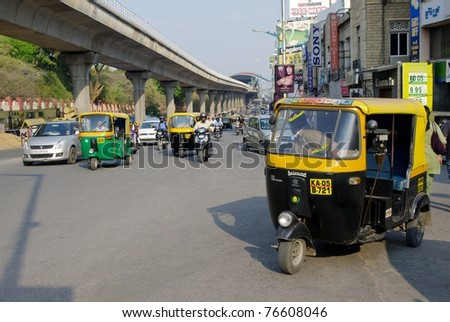 BANGALORE, INDIA - MARCH 21: Auto rickshaw taxis on March 21, 2011, M.G. road, Bangalore, India. These iconic taxis have recently been fitted with CNG powered engines in an effort to reduce pollution