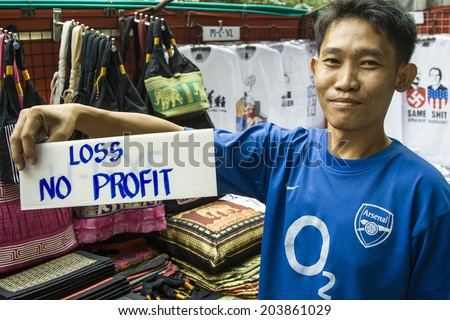 BANGKOG, THAILAND - JAN 9, 2008: man sells his traditional blankets in Bangkok, Thailand.  There are hundreds of street markets in Bangkok with clothings and textiles for tourists. - stock photo