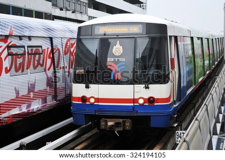 BANGKOK - APR 12: A BTS Skytrain runs on elevated rails above Sukhumvit Road on Apr 12, 2013 in Bangkok, Thailand. Each train of the mass transport rail network can carry over 1,000.  - stock photo