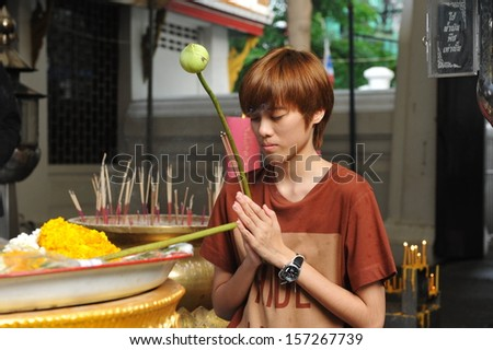 BANGKOK - APR 12: An unidentified woman prays while taking part in a merit making ceremony at a Buddhist temple during Songkran, or Thai New Year, celebrations on Apr 12, 2013 in Bangkok, Thailand. - stock photo