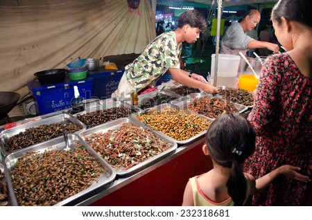 BANGKOK - APRIL 6. An unidentified man selling fried insects at flea market on April 6, 2014 in Bangkok, Thailand. - stock photo