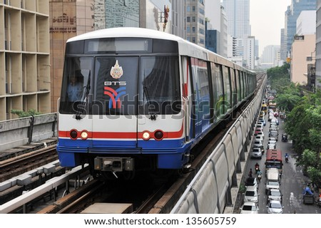 BANGKOK - APRIL 12: BTS Skytrain on elevated rails above Silom Road on April 12, 2013 in Bangkok, Thailand. Each train of the mass transport rail network can carry over 1,000 passengers. - stock photo