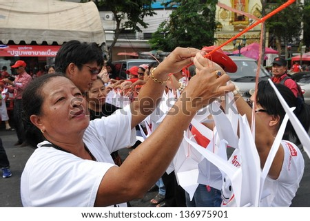 BANGKOK - APRIL 10: Red shirt protesters rally at Democracy Monument in remembrance of violent clashes that claimed 26 lives three years ago to the day on April 10, 2013 in Bangkok, Thailand. - stock photo