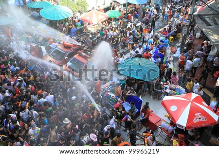 BANGKOK - APRIL 13: Stream of water over the crowd of people during celebrating the traditional Songkran New Year Festival, April 13, 2012, Silom road, Bangkok, Thailand.