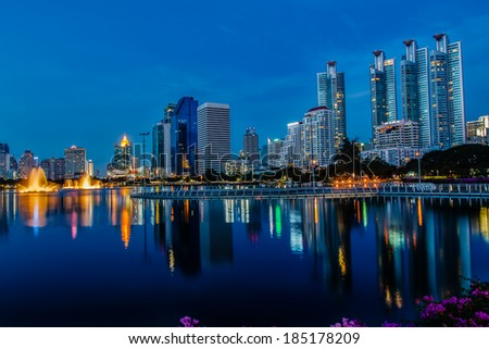 Bangkok at night with  light commercial buildings reflected on the surface of the water of thailand
