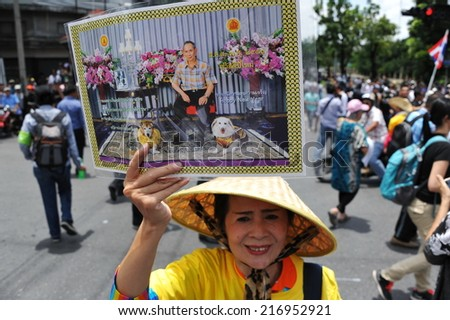 BANGKOK - AUG 7: A royalist anti-amnesty bill protester holds a picture of the Thai king during a rally near parliament on Aug 7, 2013 in Bangkok, Thailand. - stock photo