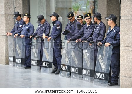 BANGKOK - AUG 17: Riot police stand guard during anti-government protest in Bangkok's shopping district on Aug 17, 2013 in Bangkok, Thailand. Protesters rallied against a controversial amnesty bill. - stock photo