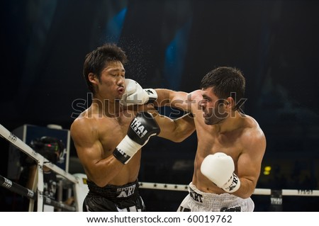 BANGKOK - AUGUST 29: Arican Fikri (R) Thai boxer from Turkey hits his opponent Miyakoshi Soichiro in an international fight competition, on August 29, 2010 in Bangkok, Thailand. - stock photo
