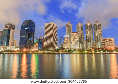 BANGKOK - AUGUST,9 : Cityscape view of modern buildings at Benjakitti garden at twilight time where have the light of the lamps shining on the pool and buildings.THAILAND AUGUST,9 2015