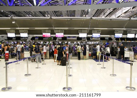 BANGKOK - AUGUST 15 : People waiting in check-in line K terminal of the Bangkok airport on August 15, 2014. Suvarnabhumi airport is world's 4th largest single-building airport terminal. - stock photo