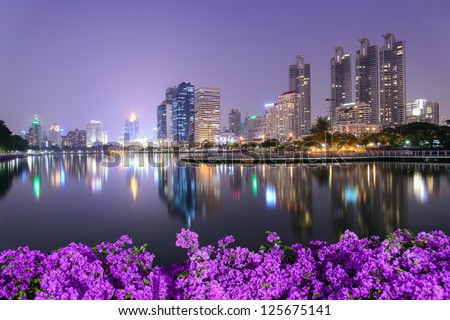 Bangkok city downtown at night with Bougainvillea flower foreground - stock photo
