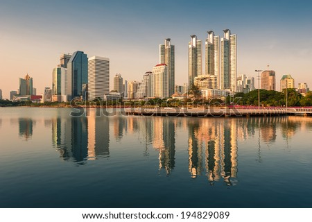 Bangkok city downtown at sunset with reflection of skyline, Benjakitti Park,Bangkok,Thailand  - stock photo