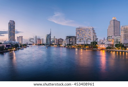 Bangkok city with business building and water traffic at chao praya river in twilight sunset, street view on Taksin Bridge, Road Phrachao Taksin, thailand.