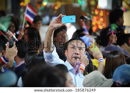 BANGKOK - DEC 20: An unidentified anti government protester takes a selfie during a several thousand strong rally through the Thai capital's business district on Dec 20, 2013 in Bangkok, Thailand. - stock photo