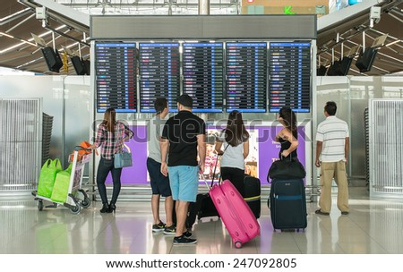 BANGKOK - Dec 30 : Many traveler with backpack in airport near flight timetable on Dec 30,2014 in Bangkok, Thailand. - stock photo