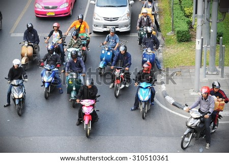 BANGKOK - DEC 23: Motorcyclists and cars wait at a junction during rush hour on Dec 23, 2011 in Bangkok, Thailand. Motorcycles are often the transport of choice for Bangkok's heavily congested roads. - stock photo