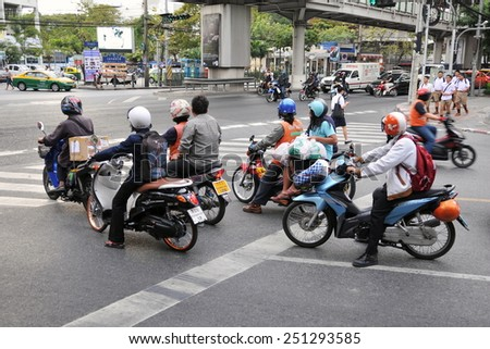 BANGKOK - DEC 17: Motorcyclists wait at a junction during rush hour on Dec 17, 2010 in Bangkok, Thailand. Motorcycles are often the transport of choice for Bangkok's heavily congested roads.  - stock photo