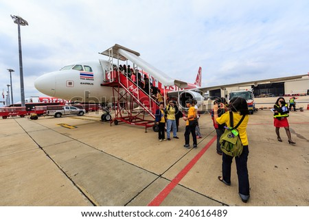 BANGKOK - DEC 5: Passenger boarding Air Asia at Don Mueang International Airport on Dec 5, 2014 in Bangkok. is a Malaysian low-cost airline headquartered near Kuala Lumpur, Malaysia. - stock photo