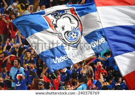 BANGKOK, DEC 10:Unidentified Thai fans cheer in action during the competition 2014 AFF Suzuki Cup between Thailand and Philippines at Rajamangala stadium on December 10, 2014 in Bangkok, Thailand.  - stock photo