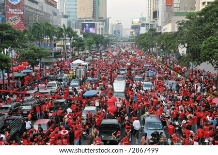 BANGKOK - DECEMBER 19: An estimated 10,000 anti-government red-shirts defy an emergency decree to protest at Ratchaprasong Junction on December 19, 2010 in Bangkok, Thailand. - stock photo