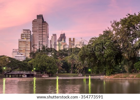 BANGKOK - DECEMBER 18: Skyscraper building cityscape with reflection on lake in park in Bangkok, Thailand, in evening twilight sky, was taken on December 18, 2015.