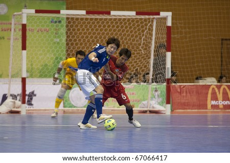 BANGKOK - DECEMBER 12 : Thailand vs Japan Bangkok Futsal Super Match 2010.Tomoaki Watanabe(Blue) and Thananchai Chomboon(Red) on DECEMBER 11 -12 2010 in Bangkok Thailand. - stock photo