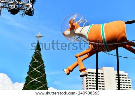 BANGKOK- 28 December 2014 : The huge Christmas tree in front of Central World Plaza, Bangkok One of the shopping area in Thailand. The tree is as tall as the building. This year is a Snoopy Theme - stock photo