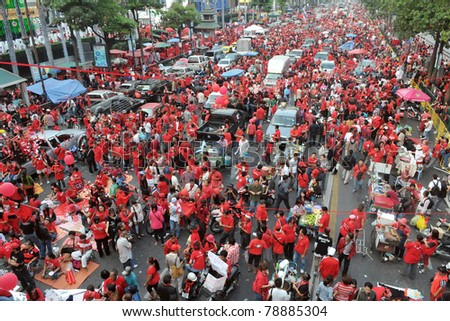 BANGKOK - DECEMBER 19: Thousands of anti-government red-shirt protesters defy an emergency decree to rally at Ratchaprasong Junction on December 19, 2010 in Bangkok, Thailand. - stock photo