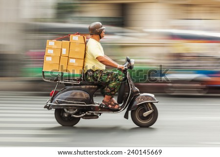 BANGKOK - DECEMBER 12: unidentified motorcyclist rides an overloaded scooter on a city street on Dec 12, 2014 in Bangkok, Thailand. The use of motorcycles to transport goods is commonplace in Bangkok. - stock photo