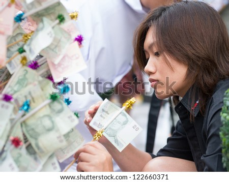 BANGKOK - DECEMBER 23: Woman giving alms, a 20 baht note during a mass alms giving in celebration of the 2,600th anniversary of Lord Buddha's enlightenment on December 23, 2012 in Bangkok, Thailand.