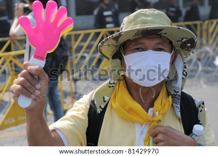 BANGKOK - FEB 11: A yellow-shirt or People's Alliance for Democracy (PAD) supporter at a large anti-government rally outside Government House on Feb 11, 2011 in Bangkok, Thailand. - stock photo
