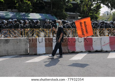 BANGKOK - FEB 11: A yellow-shirt or People's Alliance for Democracy protester walks past a barricade outside Government House as scores of riot police stand guard Feb 11, 2011 in Bangkok, Thailand. - stock photo