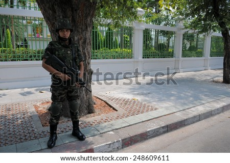 BANGKOK - FEB 11: An armed Thai soldiers stands guard on a street near government buildings as anti election Yellow Shirt protesters hold a rally in the vicinity on Feb 11, 2011 in Bangkok, Thailand. - stock photo