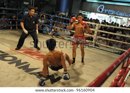 BANGKOK - FEB 22: An unidentified Muay Thai fighter is knocked to the mat during a Thai kickboxing match at MBK Fight Night on Feb 22, 2012 in Bangkok, Thailand.