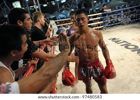 BANGKOK - FEB 22: An unidentified Muay Thai fighter returns to his corner after a Thai kickboxing match at MBK Fight Night on Feb 22, 2012 in Bangkok, Thailand. - stock photo