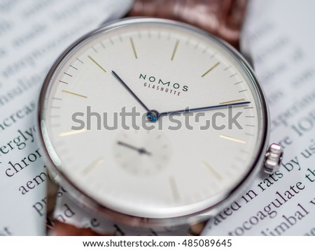 BANGKOK - FEBRUARY 9 : Nomos dress watch, silver dial, blued steel hands, on English paper background, selective focus on its brand name, was taken on February 9, 2016, in Bangkok, Thailand