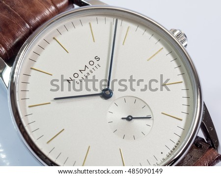 BANGKOK - FEBRUARY 9 : Nomos dress watch, silver dial with blued steel hands, on white background, selective focus on its brand name, was taken on February 9, 2016, in Bangkok, Thailand