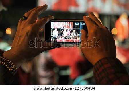 BANGKOK - JAN 29: A protester uses a smartphone to photograph a red-shirt rally on the Royal Plaza on Jan 29, 2013 in Bangkok, Thailand. Protesters gathered to demand political prisoners be freed.
